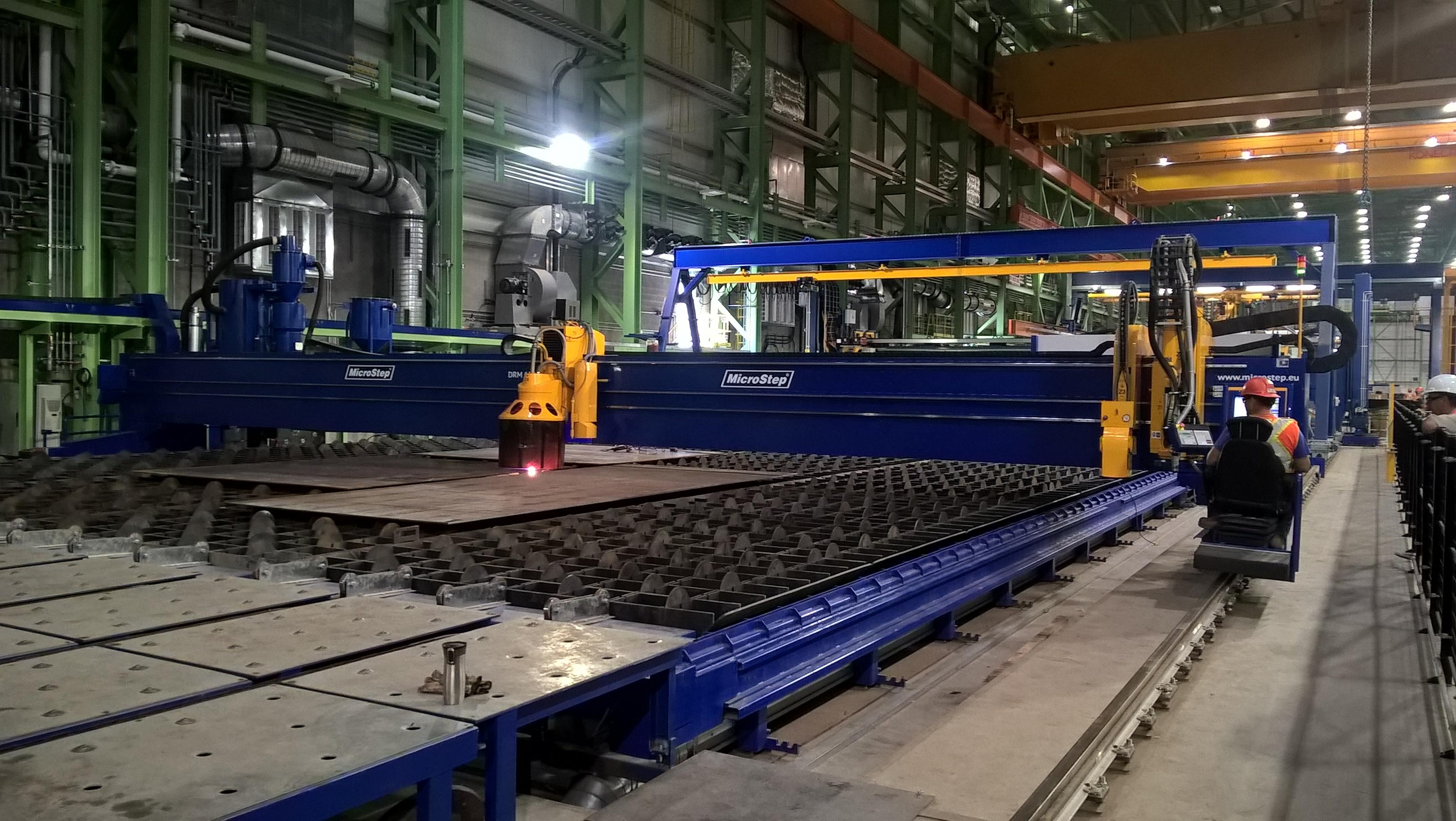 Rezac� stroj typu DRM s prac. ��rkou 13 m ako s��as� panelovej linky v kanadskej lodenici � �peci�lne rie�enie s pieskovacou hlavou.